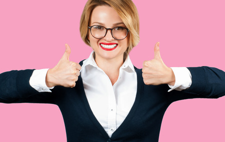 Business woman is showing thumb up. Beautiful student girl with thumbs up on pink background