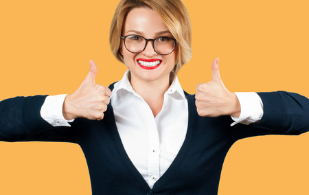 Business woman is showing thumb up. Beautiful student girl with thumbs up on yellow background
