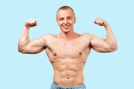 Diet and weight loss concept. Fitness muscular man showing six pack on blue background