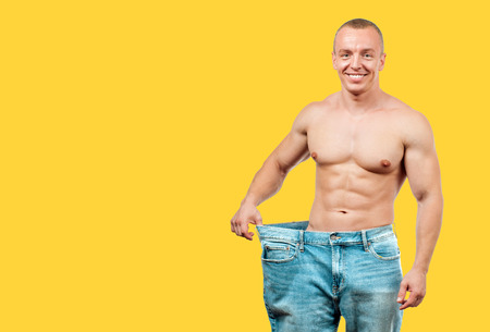 Man wearing big jeans after diet, weight loss concept on yellow background
