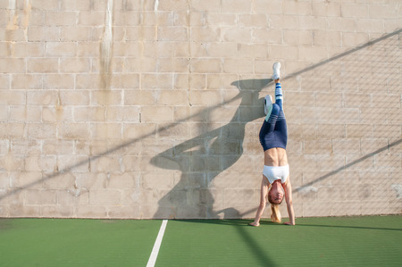 Healthy lifestyle and yoga concepts. Fitness woman in sportswear is doing exercise, stretches on the wall Stok Fotoğraf