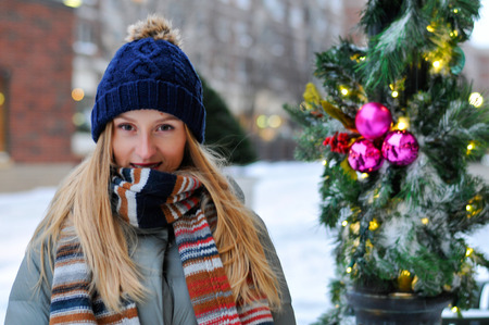 Happy winter time in city of charming girl walking on street enjoying cheerful mood and Christmas holidays Фото со стока - 112043664