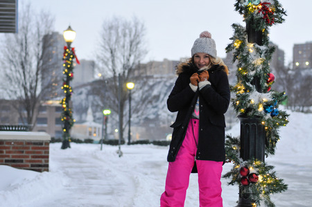 Happy winter time in city of charming girl walking on street enjoying cheerful mood and Christmas holidays Фото со стока