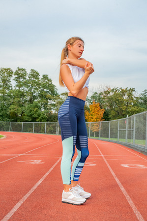 Fitness woman warming up exercises. Woman has neck pain and shoulders after running