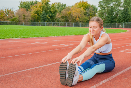 Healthy lifestyle. Fitness woman stretching legs before run on outdoors