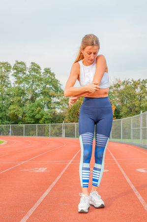 Athletic woman on running track has elbow pain during workout