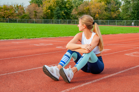 Woman runner taking a rest after run sitting on the running track