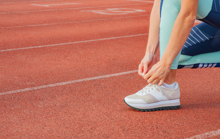 Sports woman runner tying shoelaces. Woman lacing her sneakers on a stadium running track. Workout concept Stock Photo