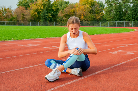 Sport knee injury. Woman has pain in knee after run outdoors at stadium