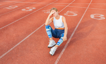Tired woman runner taking a rest after run sitting on the running track