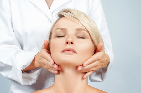 Beauty and facial treatment. Beautiful woman with clean perfect skin is getting face massage Stock Photo