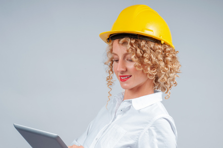 Business woman engineer in yellow safety helmet is looking to tablet computer
