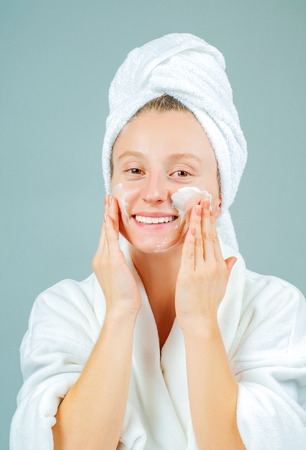 Facial care. Perfect fresh clean skin concept. Young beautiful woman washing her face. Фото со стока