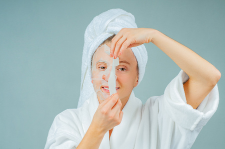 Facial care and beauty treatments. Beautiful woman with a sheet moisturizing mask on her face. Cosmetic procedure.