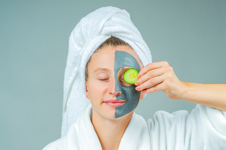 Spa Clay Mask. Beautiful young woman with clay facial mask with cucumbers on eyes. Skincare and beauty Concept. Фото со стока