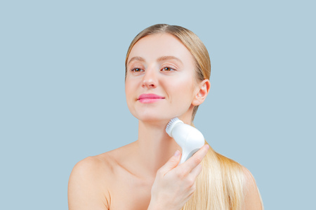 Beautiful woman is washing face skin with brush. Facial beauty treatment concept.