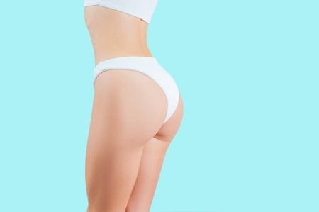 Slim woman body. Beautiful woman showing perfect buttocks in underwear on pastel blue background
