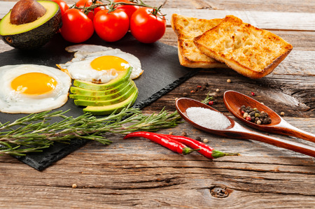 Fried egg. In the course of making breakfast with fried eggs and fresh vegetable Stock Photo
