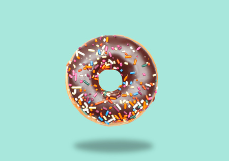 Chocolate donut with icing on pastel green background.