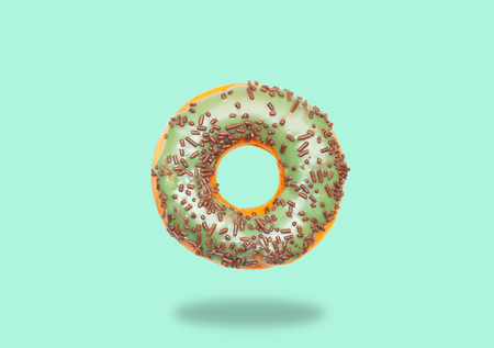 Green donut with icing on pastel green background. Imagens