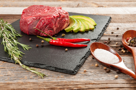 Raw beef steak and spices for cooking. Fresh meat on slate black board. Stok Fotoğraf