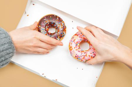 Kobiece ręce bierze kolorowe pączki. Ręce chwytają dwa ostatnie pączki w pudełku na pastelowym tle. Zdjęcie Seryjne