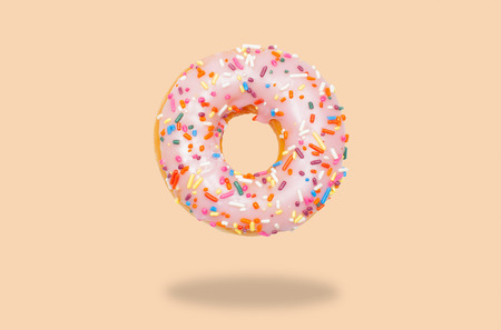 Pink donut with icing on pastel background. Imagens