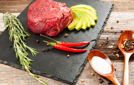 Raw beef steak and spices for cooking. Fresh meat on slate black board. Stock Photo