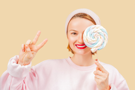 Smiling woman is holding candy lollipop. Cheerful woman hiding out eye with lollipop on pastel background