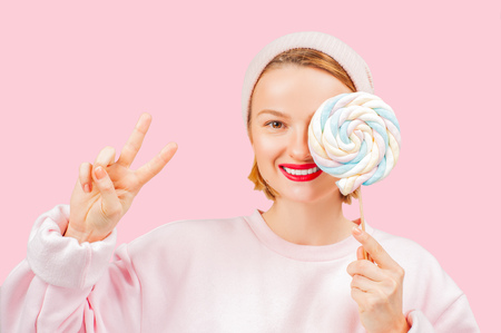 Smiling woman is holding candy lollipop. Cheerful woman hiding out eye with lollipop on pastel pink background