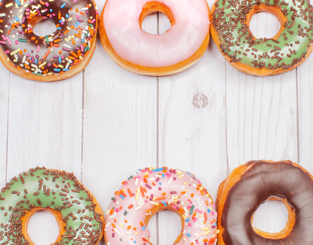 Colorful donuts with icing on wood background. Imagens