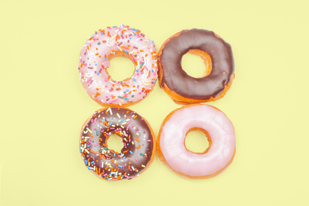 Colorful donuts with icing on pastel yellow background.