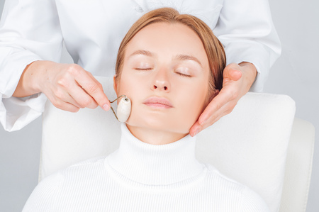 Face massage. Beautiful woman having facial beauty treatment, cosmetologist massaging chin with jade rollers. 스톡 콘텐츠