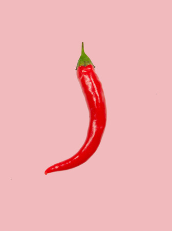 Fresh red chili pepper on pink pastel background