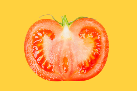Half tomato levitate in air on yellow pastel background.