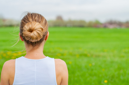 Beautiful young woman is practicing yoga on the grass. View of the back of a woman's head and shoulders Banco de Imagens