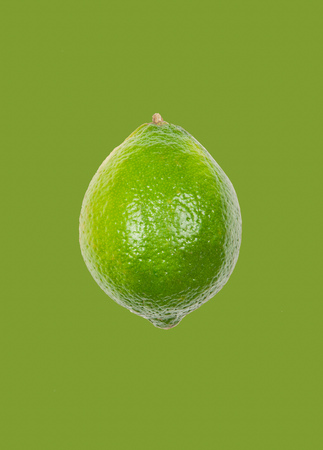 Fresh lime levitate in air on green background. Concept of fruit levitation.
