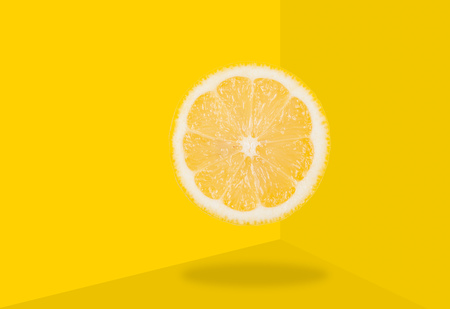 Half lemon levitate in air on yellow background. Concept of fruit levitation.