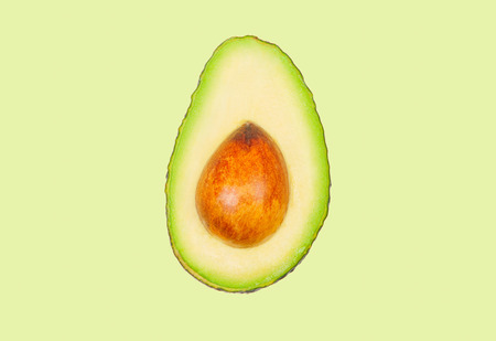 Half avocado levitate in air on green pastel background. Concept of vegetable levitation.