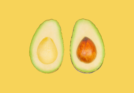 Half avocados levitate in air on yellow pastel background. Concept of vegetable levitation. Banco de Imagens