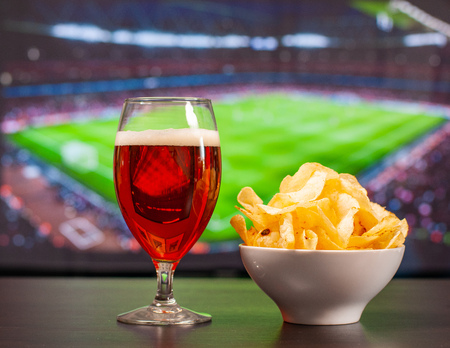 Beer glasses and chips in front of tv, football at home, soccer supporters Stock Photo
