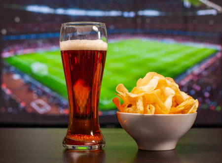 Beer glasses and chips in front of tv, football at home, soccer supporters