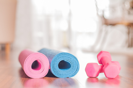 Yoga mats and dumbbells on wooden floor. Healthy lifestyle concept