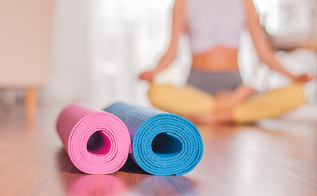 Yoga mats on wooden floor and blurred female body at the background. Healthy lifestyle concept