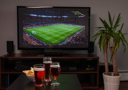 Beer glasses and chips in front of tv, football at home, soccer supporters Archivio Fotografico