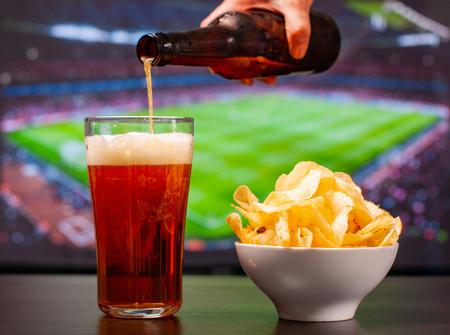 Bicchieri di birra e patatine davanti alla tv, calcio a casa, tifosi di calcio Archivio Fotografico