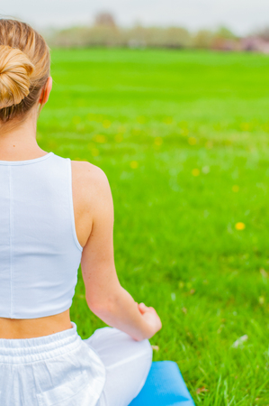 Meditation. Woman is meditating sitting in Lotus pose on grass at the park. Girl doing Ardha Padmasana pose. Stock Photo