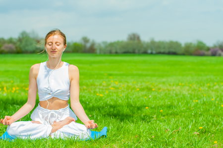 Beautiful young woman is practicing yoga or meditating sitting in Lotus pose on grass at the park.  Girl doing Padmasana pose. Stock Photo
