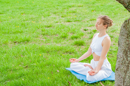 Beautiful young woman is practicing yoga or meditating sitting in Lotus pose on grass at the park.  Girl doing Padmasana pose. Фото со стока
