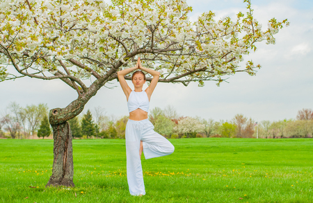 Woman meditating in yoga vrksasana tree pose at the park. Meditation concept